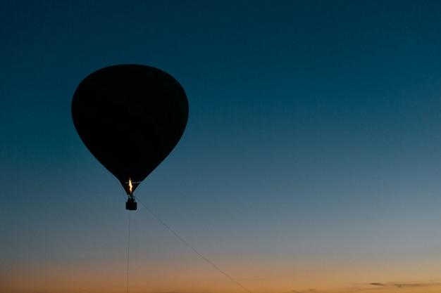 Силуэт летающего воздушного шара в ночном небе
