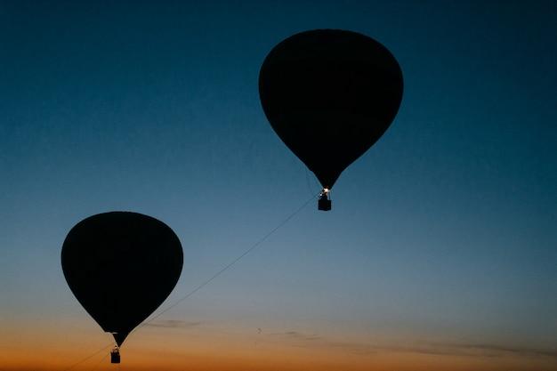 Силуэт летающих шаров в сумеречном небе