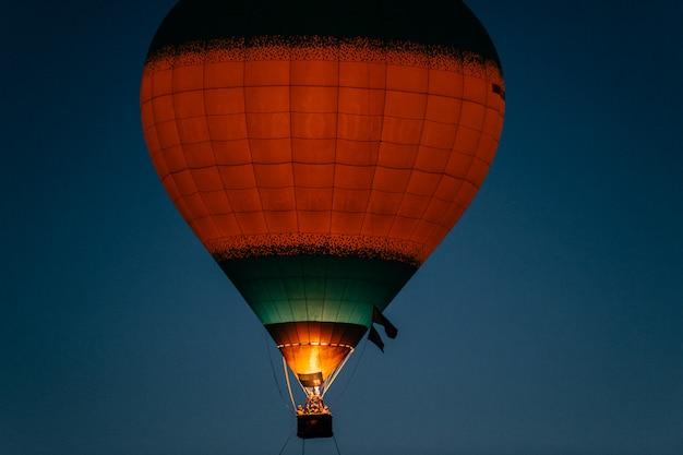 Светящийся и мигающий полет на воздушном шаре с людьми в ночном небе