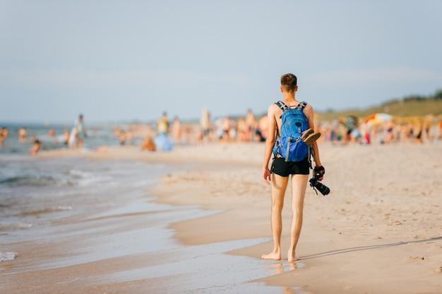 ビーチに沿って歩く彼の手でカメラを持つ孤独な写真家