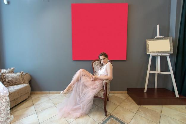 スタジオでリラックスしたペニョワールランジェリーの若い白人の花嫁。花嫁の朝