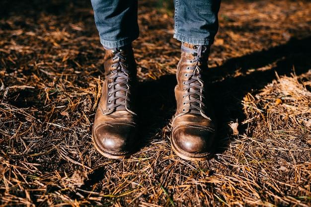 秋の地面にビンテージレザーブーツの男性の足でのトップビュー
