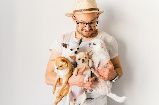 Мужчина в соломенной шляпе держит в руках четырех щенков чихуахуа