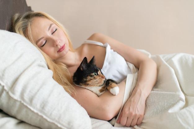 Молодая девушка спит на кровати с прекрасным котенком