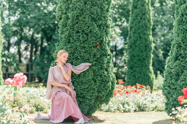 日当たりの良い公園でポーズをとる演劇的なドレスの若い優雅な女性バレエダンサー