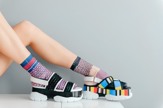 ファッショナブルな靴とカラフルな靴下で美しい女性の足