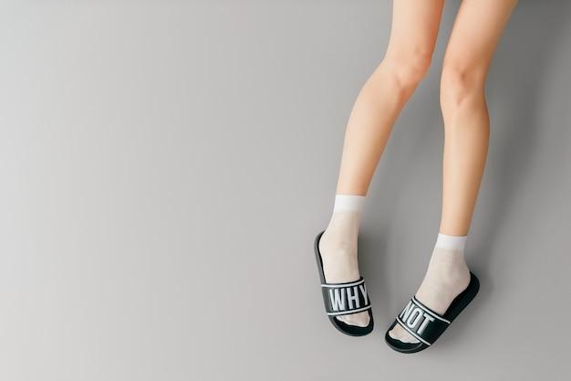 Красивые женские ножки в белых носках и модных тапочках