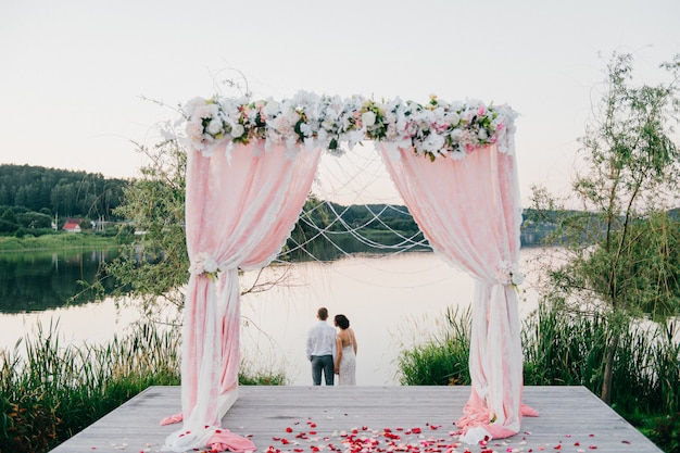 結婚式のアーチの後ろに立って、夏の日没の美しい自然の風景を楽しんでいる結婚式のカップルの後ろからロマンチックな肖像画