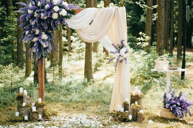 青い花と森に立っている装飾的な要素を持つ美しい結婚式のアーチ。素朴なスタイルの結婚式の風景
