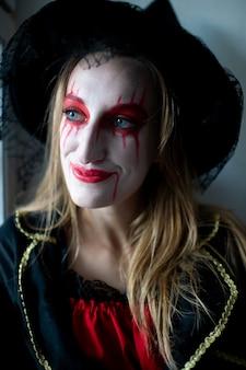 明るい化粧と漏れている口紅を持つ魔女としてブロンドの髪を持つ少女の肖像画は、不思議なことに側に見えます。