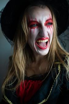 明るいメイクと漏れている口紅を持つ魔女として、公正な髪を持つ謎の少女のポートレートは、神秘的に広い笑顔で横に見えます。