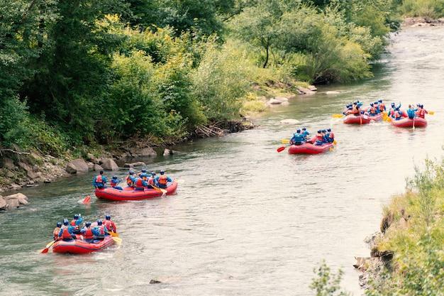 川でラフティングをしている男女のグループ。エクストリームウォータースポーツ
