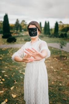夏の公園で彼女の手でジェスチャーを示す創造的な顔アートとウェディングドレスの奇妙な女性