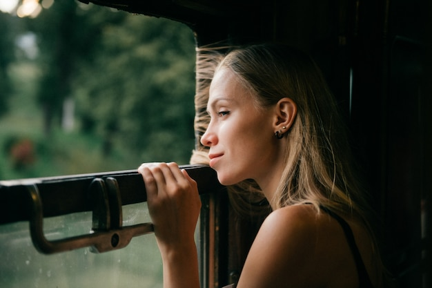 Атмосферный образ жизни портрет молодой красивой блондинки, смотрящей из окна на поезд