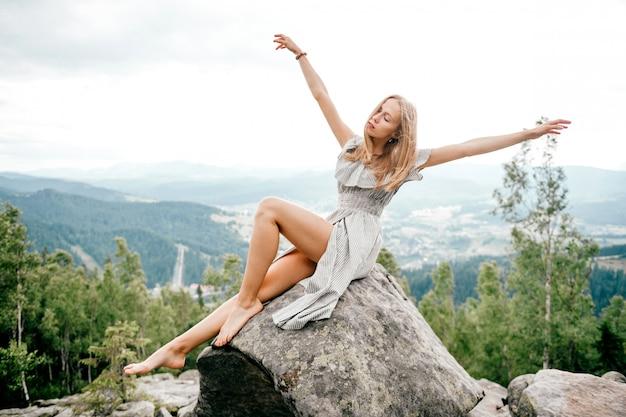Усаживание молодых красивых длинных волос белокурое на камне на горе с живописным взглядом на холмах и облачном небе.