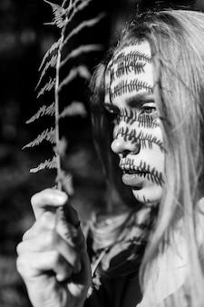 Очаровательная девушка с красивым рисунком тени от солнечного света, падающего на ее лицо через папоротниковую ветвь.