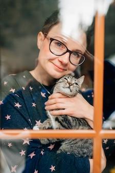 Жизнерадостная женщина с красивым лицом держит на руках милую кошку и смотрит в окно