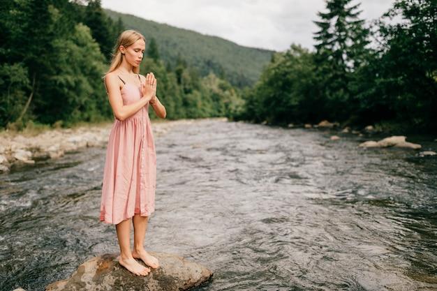 Молодая девушка молится у камня в реке