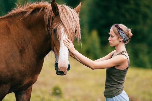 Молодая красивая девушка обнимает лошадь на природе