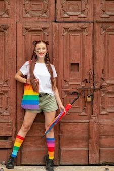古いドアにポーズのカラフルな服で両性愛の女の子。