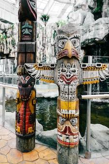 伝統的なインドのトーテム。トーテムポールの彫刻芸術。古代の木製マスク。マヤとアステカの象徴的な宗教的な神々が直面しています。