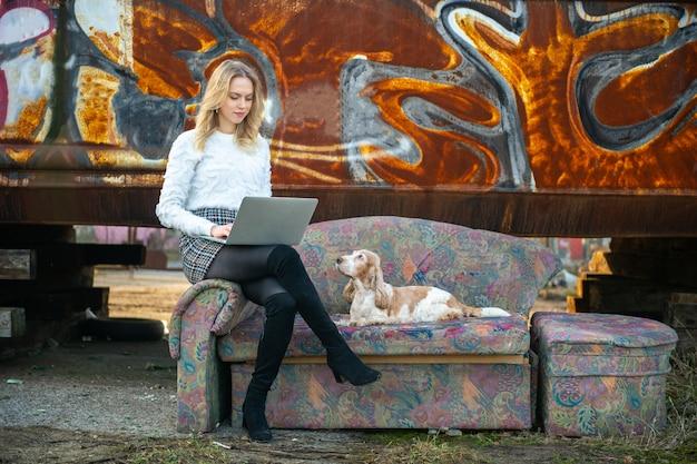 Жизнерадостная кавказская девушка фрилансера сидя на старом кресле над ржавой стеной граффити и используя компьтер-книжку с ее симпатичной собакой кокер-спаниеля
