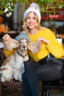 Жизнерадостная женщина в желтом свитере сидит на стуле в кафе и растягивает широкие уши своего забавного щенка кокер-спаниеля в серой шляпе