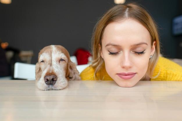 ブロンドの女の子と彼女のコッカースパニエルの子犬の頭は一緒に目を閉じてテーブルの上に横たわっています。