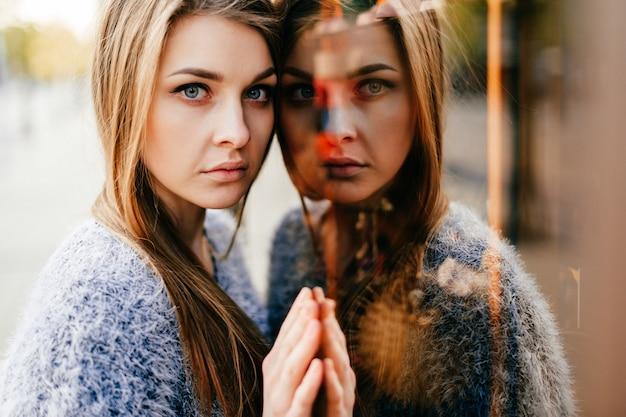 ミラーウィンドウで驚くほど若い女の子の自己反射の肖像画。自我の概念を変える。