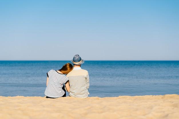一緒にビーチに座って海を見て愛するカップルの後ろからの肖像画。