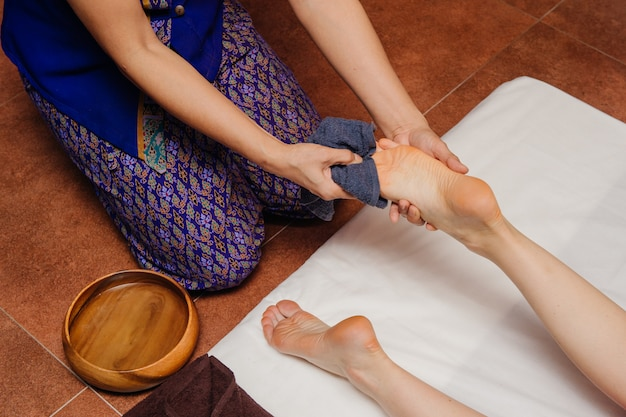 アジアの衣装を着たタイのマッサージ師は、女性の足で伝統的なスパプロシージャを作ります。