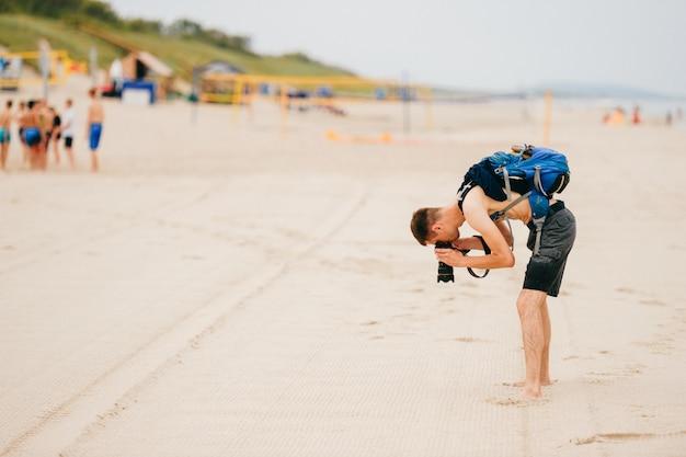 男は身を乗り出し、ビーチで砂の写真を撮ります。