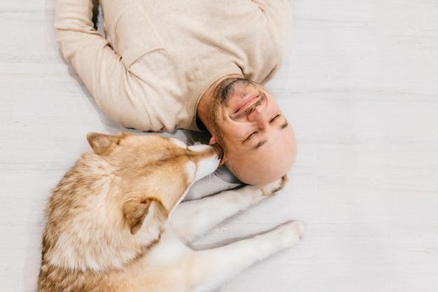 愛らしいハスキーの子犬と床に一緒に横になっている幸せな笑みを浮かべて男。