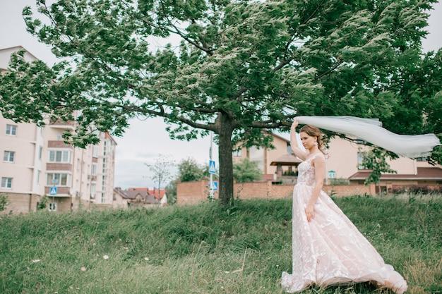 屋外ポーズ白いウェディングドレスで美しい若い花嫁