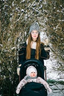 雪に覆われた冬の公園でベビーカーで娘と歩いてスタイリッシュな若い母親。