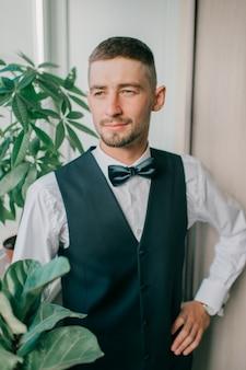 Жених в костюме и галстуке-бабочке в помещении