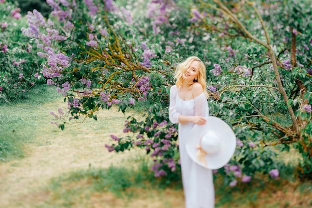 白のエレガントなドレスと咲く公園でポーズをとる帽子のかなり若い女性。