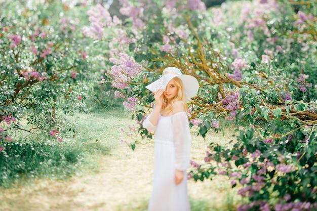 エレガントな白のドレスと帽子が咲く公園でポーズをとって、かなり優しい若い女性。