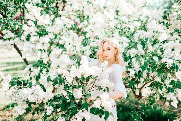 日当たりの良い公園でポーズをとって白いドレスの若い金髪モデルの女性。