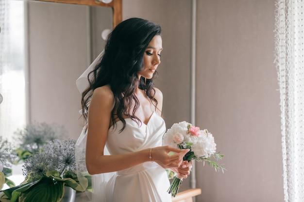 白いウェディングドレスの屋内ポートレートの美しい若い花嫁。