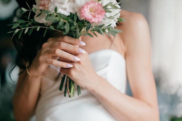 ウェディングブーケと花嫁の手のクローズアップ。