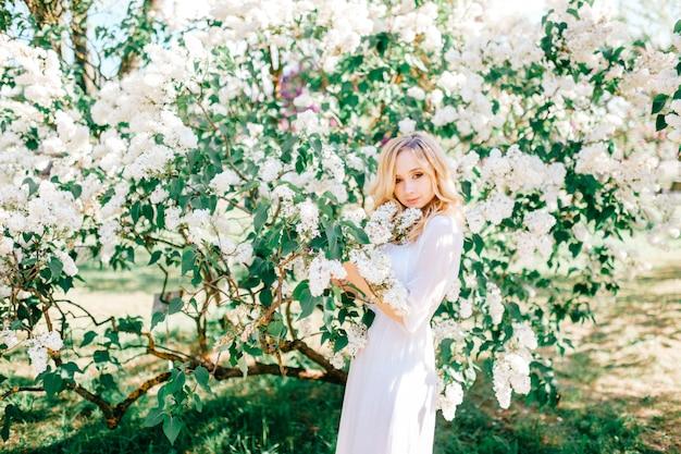 ライラックの茂みに咲くのきれいな女性。