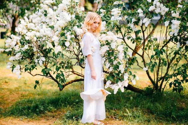 日当たりの良い公園でポーズをとって白いドレスの若いブロンドの女性。