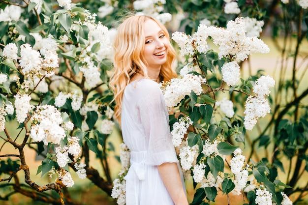 日当たりの良い公園でポーズをとって白いドレスを着た若い金髪笑顔の女性。