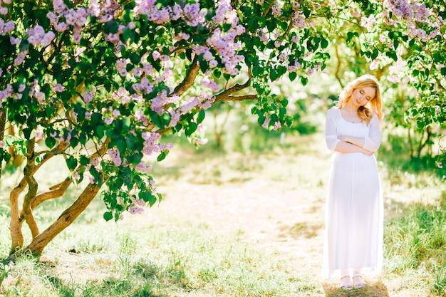 夏の日当たりの良い公園でポーズをとって白いドレスで美しい若いブロンドの女性。