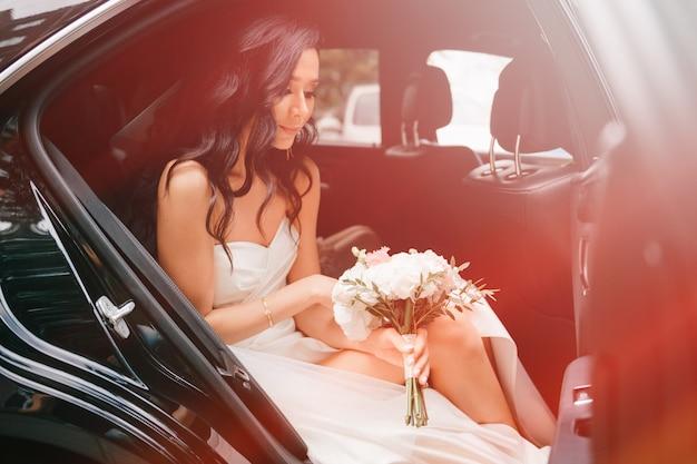 Улыбающаяся невеста в элегантном белом платье держит букет цветов и смотрит из машины