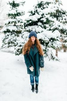 スタイリッシュな若い、かなりブルネットの女性が雪に覆われた冬の公園でポーズします。