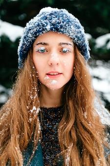 彼女の顔を覆っている雪で面白いと若い長い髪のブルネットのクローズアップの肖像画