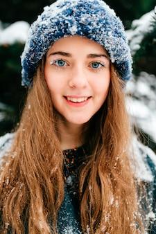 冬の公園で彼女の顔を覆っている雪でかなり笑顔の若いブルネットの肖像画