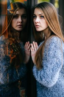 青い目をした驚くべき若い女性の自己反射の肖像画。